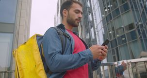 Closeup portrait of caucasian delivery man standing with backpack using navigation app on phone in city outdoors with. Cityscrapers stock video footage