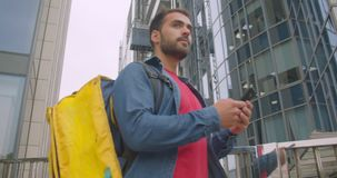 Closeup portrait of caucasian delivery man standing with backpack using navigation app on phone in city outdoors with. Modern buildings stock footage