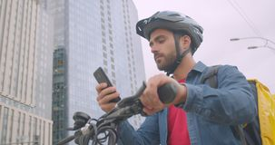 Closeup portrait of caucasian delivery man standing with kick scooter and backpack using navigation app on phone in city. Outdoors stock video