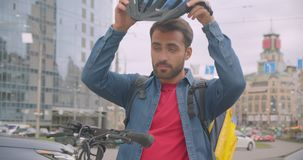 Closeup portrait of caucasian delivery man standing with kick scooter helmet and backpack using navigation app on phone. In city outdoors stock footage