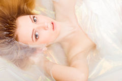 Closeup portrait of charming young blond woman beautiful girl is in shining water looking at the camera Stock Photography