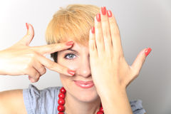 Closeup portrait of charming young woman peeking though her fingers Stock Images