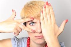 Closeup portrait of charming young woman peeking though her fingers Stock Photo