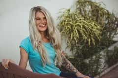Closeup portrait of cheerful blonde woman in a turquoise t-shirt smiles a perfect smile. Modern woman. Turquoise color royalty free stock photo