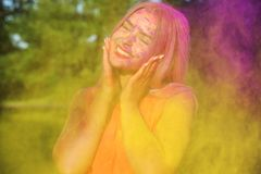 Closeup portrait of cheerful young woman having fun in a cloud of yellow dry Holi paint stock image