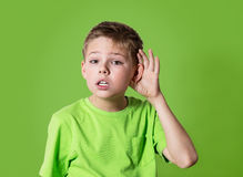Closeup portrait child hearing something, parents talk, gossips, hand to ear gesture isolated on green background. Curious boy listens. Closeup portrait child royalty free stock photo
