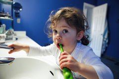 Closeup portrait of  child toddler girl in bathroom toilet washing face hands brushing teeth with toothbrash Stock Image