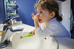 Closeup portrait of  child toddler girl in bathroom toilet washing face hands brushing teeth with toothbrash playing Stock Photo
