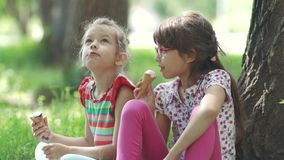 Closeup portrait of children sitting on the grass in the Park. girlfriends eating ice cream and having fun talking to stock video