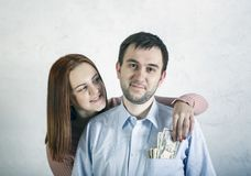 Closeup portrait couple, excited woman, girlfriend pulling money out of man pocket, he looks skeptical, surprised, Shopping lover royalty free stock photo