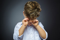 Closeup Portrait of crying boy with astonished expression while standing against grey background Royalty Free Stock Photography