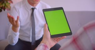 Closeup portrait of customer service manager talking to client holding tablet with green chroma key screen in office.  stock video footage