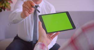 Closeup portrait of customer service manager talking to client holding tablet with green screen in office.  stock footage
