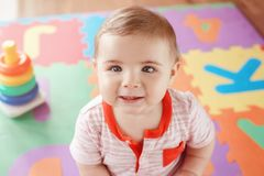 Closeup portrait of cute adorable blond Caucasian smiling child boy with blue eyes. Sitting on floor in kids children room. Little baby playing with toys on royalty free stock photos