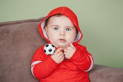 Child sitting on couch and holding football soccer toy Royalty Free Stock Photography