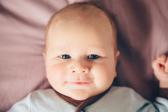 Closeup portrait of cute adorable funny white Caucasian blond little baby boy newborn with blue eyes lying on bed Royalty Free Stock Photos