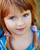 Closeup portrait of cute adorable little red-haired Caucasian girl child with blue eyes stock photo