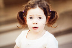 Closeup portrait of cute adorable sad upset white Caucasian toddler girl child with dark brown eyes and curly pig-tails Stock Images