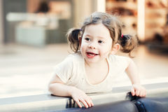 Closeup portrait of cute adorable smiling white Caucasian toddler girl child with dark brown eyes and curly pig-tails Stock Photo