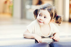Closeup portrait of cute adorable smiling white Caucasian toddler girl child with dark brown eyes and curly pig-tails Stock Images