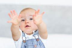 Closeup portrait of a cute baby holding out his hands Royalty Free Stock Photography
