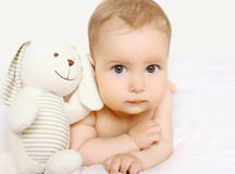 Closeup portrait of cute baby with toy lying Royalty Free Stock Photo