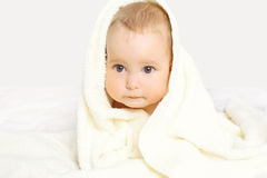Closeup portrait of cute baby under towel on the bed Royalty Free Stock Photography