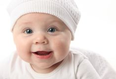Closeup portrait of cute baby wearing a hat. Closeup portrait of an adorable smiling baby wearing a white knit hat Royalty Free Stock Images