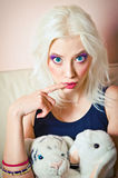 Closeup portrait of cute blonde girl with rabbit and tiger toys Stock Photos
