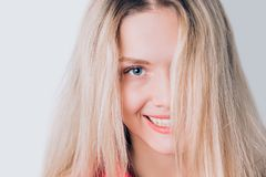Close-up portrait of beautiful cute blonde woman with long hair, clean skin, natural makeup, and white teeth royalty free stock photography