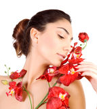 Cute female with red orchid. Closeup portrait of cute brunette female with red orchid flowers isolated on white background, luxury spa salon, aroma treatment Stock Photography