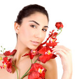 Pretty girl with red orchid flowers. Closeup portrait of cute brunette female with red orchid flowers isolated on white background, relaxing day spa, luxury Stock Photos