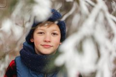 Closeup portrait of cute child boy in winter forest Stock Photo