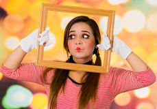 Closeup portrait of cute curious young girl clown mime holding wooden frame looking to the side Royalty Free Stock Photo