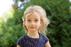 Closeup Portrait of Cute Little Blonde Girl Looking at the Camera Surprised During Summer Day in the Park. Happy Kid. Outdoors stock photo