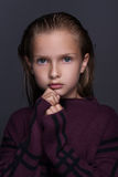 Closeup portrait of cute little girl with dark hair in studio over grey background. Stock Images