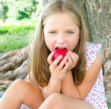 Portrait of a little girl eating apple. Closeup portrait of a cute little girl eating apple at park Royalty Free Stock Photos