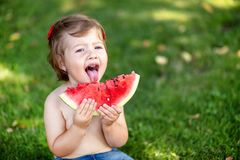 Closeup portrait of cute little girl eating watermelon on the grass in summertime Healthy snack for children. Little girl playing stock photography