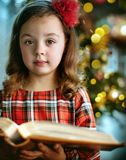 Closeup portrait of a cute, little girl holding a book royalty free stock photography