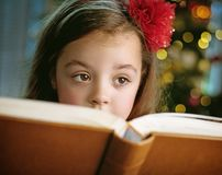 Closeup portrait of a cute, little girl reading a book stock photo