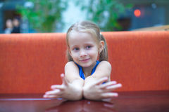 Closeup portrait of cute little girl sitting at Stock Photo