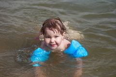 Closeup portrait of cute little girl swimming, happy child having fun in water. royalty free stock photos
