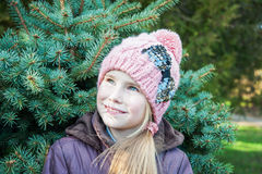 Closeup portrait of a cute little girl in winter hat looking up Stock Images