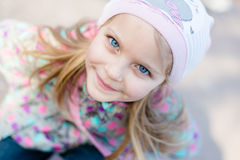 Closeup portrait of cute pretty girl with blue eyes happy smiling & looking at camera in knitwear Royalty Free Stock Photography