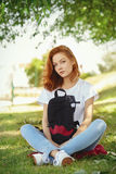 Closeup portrait  of a cute redhead hipster girl with a black backpack Stock Image