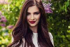 Closeup portrait of cute smiling girl outdoors. Beautiful woman face with long healthy hair and makeup Stock Images