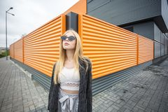 Closeup portrait of cute smiling little model girl in striped jacket and sunglasses posing near gray corrugated striped orange royalty free stock photo