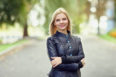 Closeup portrait of cute smiling young woman hands hugging herself posing on park path shallow depth of field royalty free stock photo