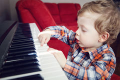 Closeup portrait of cute white Caucasian toddler boy child playing piano Royalty Free Stock Photography
