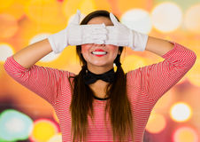 Closeup portrait of cute young girl clown mime covering her eyes. Smiling Royalty Free Stock Photo